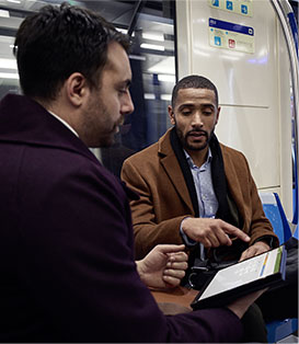 Dos hombres en el metro viendo contenido en una tablet.