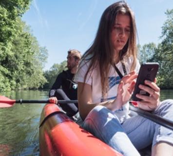 Femme dans une barque en train d'utiliser son smartphone.