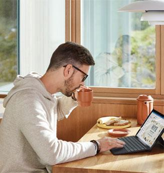 Homme en train de travailler sur un ordinateur portable chez lui.