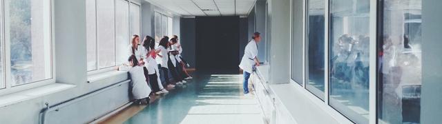 Personnel médical attendant dans un couloir.