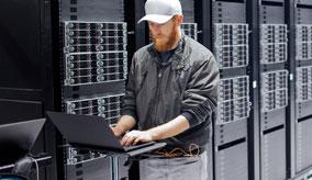 Mann mit Laptop in einem Rechenzentrum mit Link auf den Windows Server Summit